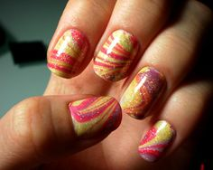 Give life to your nails with a combination of yellow, violet and red polishes created with water marble nail art design plus silver dust on top.
