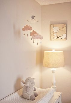 White and light pink themed nursery, a beautiful mobile and lamp setting