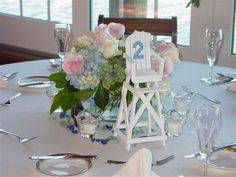 Totally cool! Love the baby blue Hydrangeas with green and pink and love the Lifeguard chair for table number for a beachy reception!