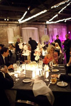 Reminds me of your the dinner and dancing space - raw concrete, colored lights would be cool ( notice fuishia color) and black and white table cloths with orchids.