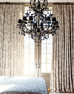Floor-to-ceiling curtains. Careful folds cover two walls of the bedroom and match the bedspread.