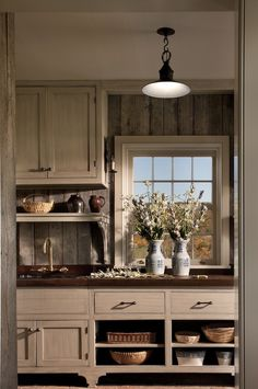 In the mudroom, walls are sheathed in weathered barn siding, with coordinating natural wood cabinetry with solid oak top.