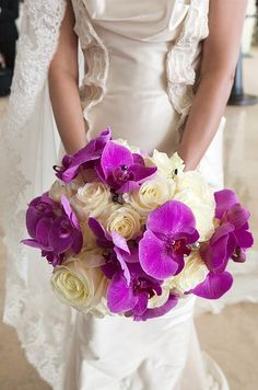 The bride carries an exotic looking bouquet of white roses and hot pink  orchids.