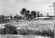 Lang Park sportsgrounds, Brisbane, Queensland, 1949 - View of Lang Park sportsground Brisbane with Hale Street on the left and Chippendall Street at the rear. The building at the left is possibly a church hall and the white roof on the right is the trolley bus depot on the corner of Milton Road and Castlemaine Street. The unfenced sportsground has some people playing on the field with a clubhouse visible to the left. Lang Park was later known as Suncorp Staduim.
