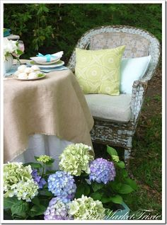 lovely setting with wicker chair, table, and hydrangeas
