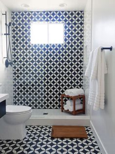 This small bathroom was remodeled with black-and-white patterned tile that's used both on the floor and one of the walls. The shower uses a glass half-door.