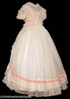 "C1865 lady's 3 pc sheer white organza gown trimmed in pleated ruffles w/Mechlin lace & deep rose coloured pull thru ribbon accents. Draped bodice w/long lappets shown wrapped around waist, & asymmetrical overskirt w/ gored front & cartridge pleated sides & back to waistband, & apron-like front overskirt w/ drawstring tied waistband w/bow & matching lace above front hem. Bodice has clear glass buttons to front closure. 38"" bust, 34"" waist & 54"" from shoulder to front hem."
