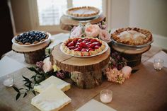 A dessert bar of various pies on a table surrounded by candles.