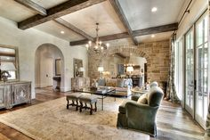 Stone accent wall family room traditional decorating ideas with green armchair wood ceiling beams