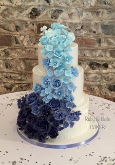 Beautiful 3 tier wedding cake with blue ombré cascade of flowers. Created by Ru