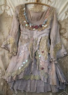 Fairytales inspired shabby chic soft linen tunic, hand dyed in shades of pale cream, ecru and sand. Reworked with antique and vintage laces- at neckline there are beautiful handmade old lace pieces, tea dyed caramel and dark cream, complemented with hand embroidered torn mauve and dusty pink silk roses, sequins and hand beading. The overskirt is split at front like at old gowns and trimmed with vintage sage bobbin lace trim, sequins and silk pieces. The bottom edge is layered with delicate…
