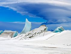 An alien-looking cloud looms over the blue shards of ice in the otherworldly Antarctic landscape being mapped by NASA's Operation IceBridge