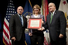 """Under Secretary of the Army Joseph W. Westphal (far right) presents the Army Decoration for Distinguished Civilian Service to former Rep. Gabrielle """"Gabby"""" Giffords (Ariz.) for """"outstanding public service and support of the Army's missions"""", Oct. 10, 2013 at the Pentagon, Washington, DC. She is joined by her husband retired Navy Capt. Mark Kelly. (U.S. Army photo by Staff Sgt. Bernardo Fuller)"""