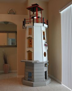 This was the first cat tower Square Paws designed and built, modeled loosely after the Louisbourg Lighthouse in Nova Scotia, Canada. This piece measures 37-1/2″ wide by 37-1/2″ deep by 109-1/2″ (over 9 feet) tall to its highest point. Our cats tend to vie for the top nesting spot and will settle for