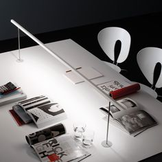 The Lineal Biblo Table Lamp by Carpyen was developed as a way to illuminate multifunctional workspaces and library tables. Made of aluminum, this table lamp is offered in three different sizes, and features a thin shade house the LED light source. Suspended Lighting, Modern Lighting, Lighting Design, Office Lighting, Shade House, Modern Fan, Cafe Tables, Under The Table, Unique Furniture