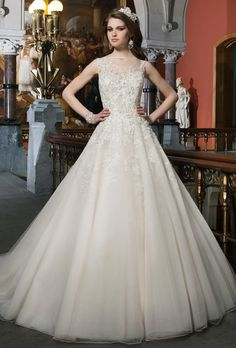 Brides: Justin Alexander. Beaded embroidered and corded lace tulle ball gown features a Sabrina illusion neckline. Style has a high beaded illusion back with regal satin buttons and a chapel length train.