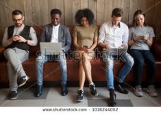 Multicultural young people using laptops and smartphones sitting in row, diverse african and caucasian millennials entertaining online obsessed with modern devices waiting in queue, gadget addiction Waiting In Queue, Young People, Photo Editing, Smartphone, Royalty Free Stock Photos, African, Branding, Entertaining, Gadget