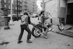 A member of the Chingalings Motorcycle Club pushes another biker at the entrance to their rent-free city-owned clubhouse in the South Bronx. ~ image copyright © Allan Tannenbaum