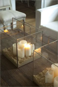 I love the big square glass containers filled with sand & candles. (Would love to know what the containers are they look fairly large). white candles, sand, and glass for extra sparkle.