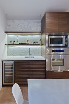 A wet bar is pared down with suspended shelves, under-cabinet lighting and a patchwork of marble tiles. The textured cabinet doors add visual interest alongside the slim wine cooler.