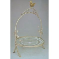 Beautiful display cake or cheese in metal beige / taupe skated with round glass.  The scenery is decorated with scrolls and a beautiful bird lying on top.