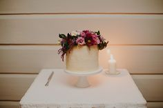 Small cake on white plate and flowers. Would look pretty with some white and cream color flowers.