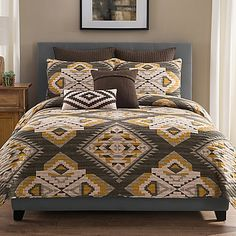 Transform your bedroom into a cabin retreat with the charming Sierra Quilt. The cozy quilt instantly creates a rustic look in any room with a Navajo-inspired geometric print in grey, mustard yellow, brown and cream.