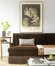 Living room with a brown velvet sofa and vintage art