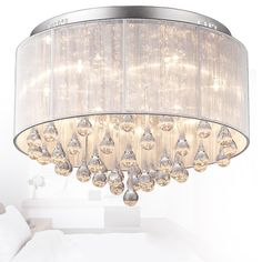 Full of grace, this flushmount ceiling light offers warm, gentle illumination. Delicate strands of clear octagon faceted crystals are surrounded by a semi-transparent organza shade to weaken the brightness from the incandescent bulbs. The exposed clear glass teardrops are hung tastefully to make this flush ceiling fixture more beautiful.