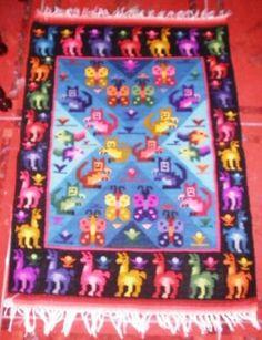 """Peruanischer Webteppich, """"4 Regionen Perus"""", 90 x 60 cm    Peruanischer Webteppich, die 4 Regionen  90 x 60 cm    Farbenfroher Webteppich, handgewebt.      Das Motiv sind die 4 Regionen Perus:    Aussen die Alpakas symbolisieren die Anden  Die Fische stehen fuer die Kueste  Die Schmetterlinge fuer den Amazonas  und die Eichhoernchen fuer die Selva, dem Landesinneren von Peru.    Liebevoll und farbenfroh handgewebt aus Merinowolle."""