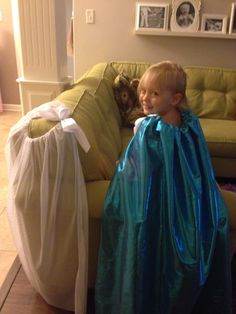 """Super easy kid capes!  I took a yard(ish) of fabric...preferably the kind you don't have to hem...and made a tube at the top.  I ran skinny elastic through and tied it off so my little one could put it on by herself over the head.  Then I decorated the opening with a sewn on bow.  She loves it!  The blue one is lame and that stuff ravels like crazy.  So instead of sewing a hem I used iron on hem.  It's holding up well. She calls it her """"let it go cape"""" and thinks she's Queen Elsa from Frozen…"""