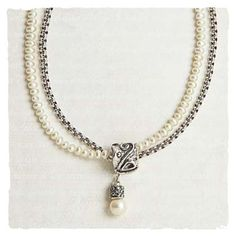 Ancient Scroll Necklace. Sterling silver is hand cast and oxidized to create a unique drop pendant of swirls and dots. With a glowing pearl dangle, it slides on double strands of freshwater pearls and rolo chain. Lobster clasp. 18 inch long chain, 1.2 inch drop.  - Arhaus Jewels