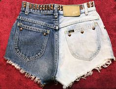 Love these awesome one of a kind restyled super high waist Lee jean cut off shorts! Captivate with the unique half and half two toned coloring and the pyramid stud hardware embellishment on the waist and pockets, a fun but subtle detail. Cut off at an angle for an ultra short, cheeky look thats perfect for summer and music festivals! Excellent condition, one missing stud (center of left back pocket), but other wise no noted flaws!  DETAILS! Label: LEE Era: 1990s Size: Extra Small Hand…
