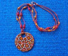 Rozkvetlá louka Náhrdelník - placka z fimo hmoty ve veselých barvách, doplněná červenými a oranžovými dřevěnými korálky.  Rubová strana jednobarevná (červená) s plastickým zdobením. Placku lze nosit otočenou lícovou nebo rubovou stranou.  Navlečeno na voskových šňůrkách se zapínáním. Délka šňůrky cca 32cm, placka má průměr 5 cm.  Dobré ráno přeji...Dobré, dobré... Jaké je dnes venku počasí? Ó...ó...ó, co to tam je? Kde? Podívejte! Jé, rozkvetly květiny u pařezu. To je nádhera...