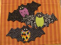 """Let's go batty this Halloween! A really cute mini quilt for your coffee mug and sweet treat!  Finished size 6 """" x 13""""  Supplies for each bat : 6"""" square Fusible Web 7"""" x 14"""" fabric rectangle for backing 7"""" x 14 black fabric rectangle for front Black thread for machine quilting and appliqué Scrap fabric in the following colors; white, black, orange or assorted Halloween fabrics for bat body and face. 2 tiny buttons for bat's eyes 7"""" x 14 """"piece of batting  4 pages of directions in US…"""