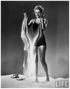 Model wearing black form-fitting bathing suit sifting sand through fingers; sandals resting on sand 1941 Gjon Mili