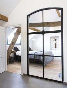 Une chambre parentale qui double sa surface grâce à une verrière intérieure composée de miroir fixée au mur le plus long de la chambre