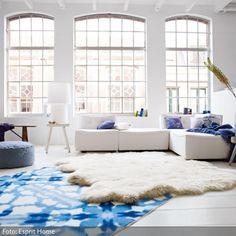 Cool und dennoch gemütlich: Die hohen, vergitterten Fenster, die cleanen, weißen Wände und der schlichte Fußboden des Wohnzimmers charakterisieren einen modernen…