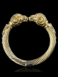 VICTORIAN ETRUSCAN STYLE GOLD RAMS HEAD BANGLE c.1870. Comprising of ribbed twisted gold bangle terminating in two textured gold ram's heads, topped by pierced scrolled gold, with scrolled ribbed horns, flanked by scrolled wire tipped by small polished gold balls.
