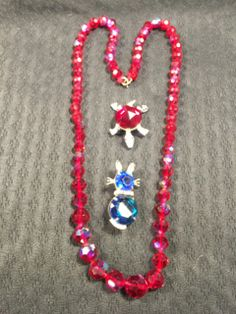 DARLING LOT OF VINTAGE JEWELS. INCLUDES A GORGEOUS CHERRY RED AURORA BOREALIS CRYSTAL NECKLACE MEASURING 24 INCHES IN LENGTH. LOT ALSO INCLUDES A PAIR OF ANIMAL BROOCHES WITH JEWELED BELLIES.