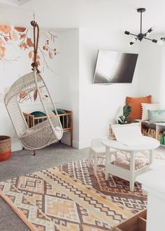 Modern white bright playroom that's organized with pops of color and a hanging chair // wallpaper and bookshelf bench with table and chairs