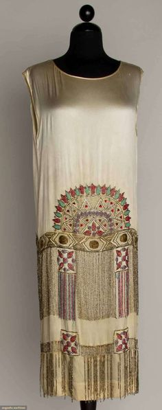 "BEADED WHITE FLAPPER DRESS, 1920s Silk satin, beaded in turquoise, gold, & red w/ 2 tiers deep fringe, B 39"", Low W 39"", L 42"", (small pull near L shoulder, 1 underarm tear at seam, missing fringe) very good."