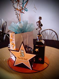 """Here's a low cost basketball centerpiece. It had a 'Hoopla"""" shopping bag, a basketball trophy from home and a table number with a fun basketball term and description. All this was sitting on a foamcore basketball circle. If you're looking for a low budget idea, this could be a cheap...yet cute...centerpiece option."""