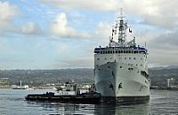 Tug boats assist in the return of the Royal Canadian Navy auxiliary oil replenishment ship HMCS Protecteur (AOR 509)
