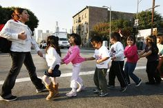 Students from the skid row charter school operated by Para Los Ninos cross the street to Gladys Park, which normally has been off-limits to children because of the number of homeless people and drug use there.