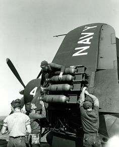 Vought F4U Corsair. Arming 100-lb. Bombs -   Ordnancemen placing arming wires on 100-lb. bombs on the wing of an F4U Corsair on board the carrier Boxer (CV 21)
