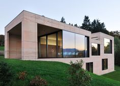 This fair-faced concrete house was designed by Arhitektura Krušec to look like rocks emerging from a sloped meadow facing the Slovenian Alps