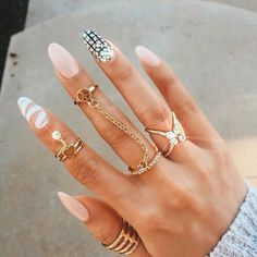 Nude polish with white ribbon accent nail (pointer finger) and checkered & diamond layered pattern with rhinestone accent nail (ring finger)