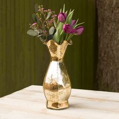 Our golden mercury glass vase adds adds enchantment to a variety of events. This metallic vessel has a fluted top and hourglass shape somewhat resembles a ball gown.