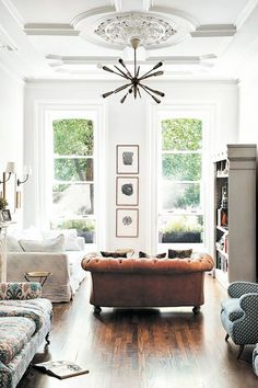 Bright living room with a tufted leather sofa, wood floors, and a statement chandelier